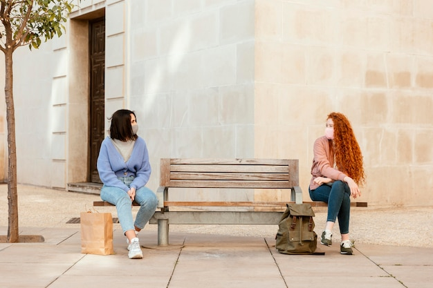 Vorderansicht von freundinnen mit gesichtsmasken draußen sitzen auf einer bank