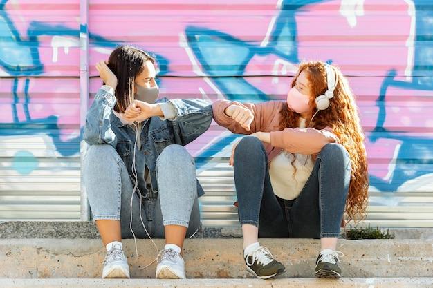 Vorderansicht von freundinnen mit gesichtsmasken im freien, die musik auf kopfhörern hören und den ellbogengruß tun