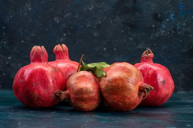 Vorderansicht von frischen roten granatäpfeln auf dunkler oberfläche