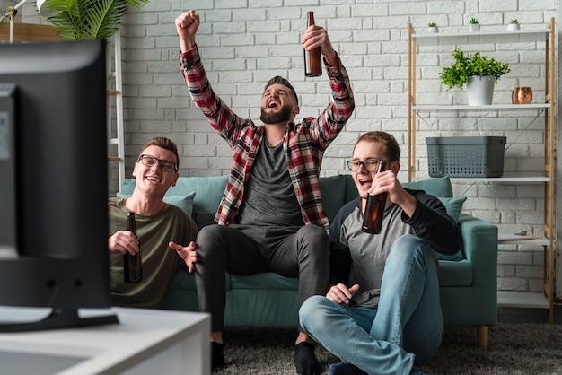Vorderansicht von fröhlichen männlichen freunden, die sport im fernsehen ansehen