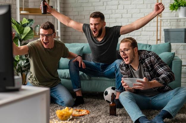 Vorderansicht von fröhlichen männlichen freunden, die zusammen sport im fernsehen schauen, während sie snacks und bier haben