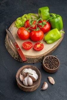 Vorderansicht von ganz geschnittenen gehackten grünen paprika und frischen tomatenmessern auf holzbrett pfefferknoblauch auf schwarzer oberfläche