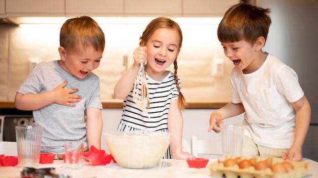 Vorderansicht von geschwistern, die zu hause kochen