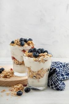 Vorderansicht von gläsern mit frühstücksflocken und joghurt