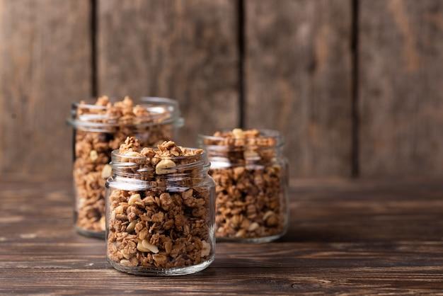Vorderansicht von gläsern mit frühstückskost aus getreide und kopienraum