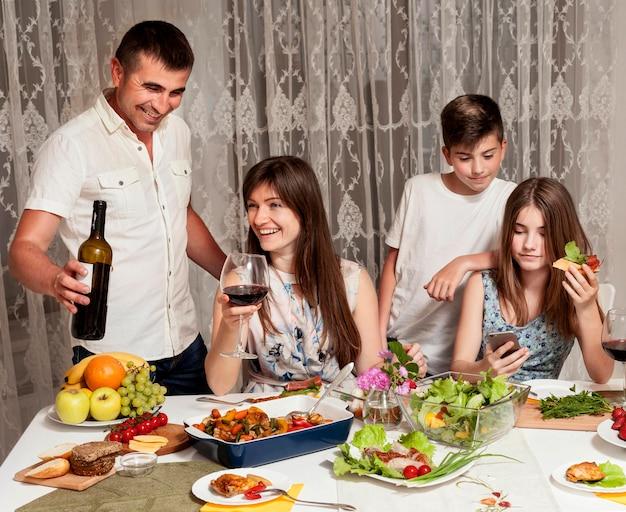 Vorderansicht von glücklichen eltern und kindern am esstisch