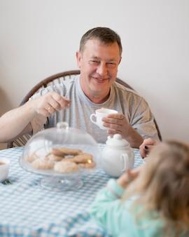 Vorderansicht von großvater und enkelin beim mittagessen