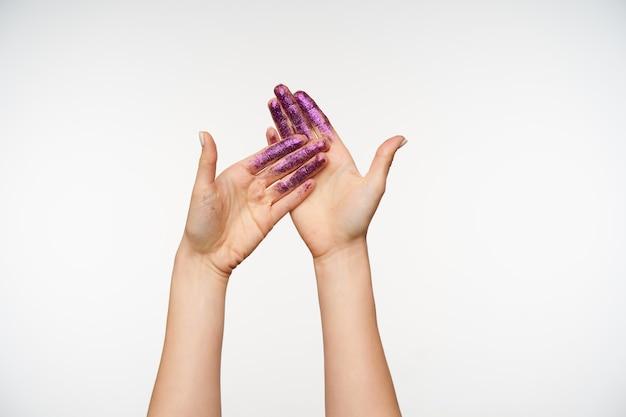 Vorderansicht von jungen hellhäutigen hübschen händen, die palmen mit violetten schimmern zeigen, während sie auf weiß isoliert stehen. menschliche hände und gestik