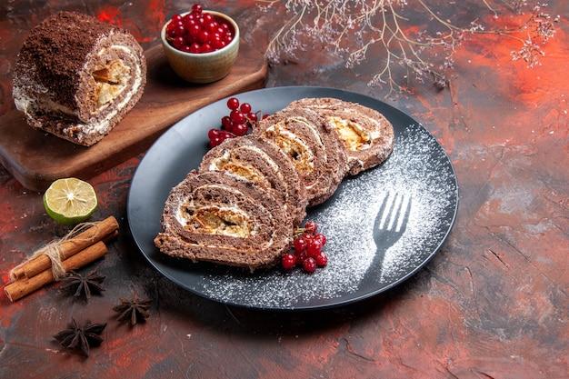 Vorderansicht von keksrollen mit roten früchten auf dunkler oberfläche