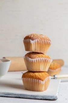 Vorderansicht von kleinen kuchen innerhalb der papierformen mit zuckerpulver auf der weißen oberfläche