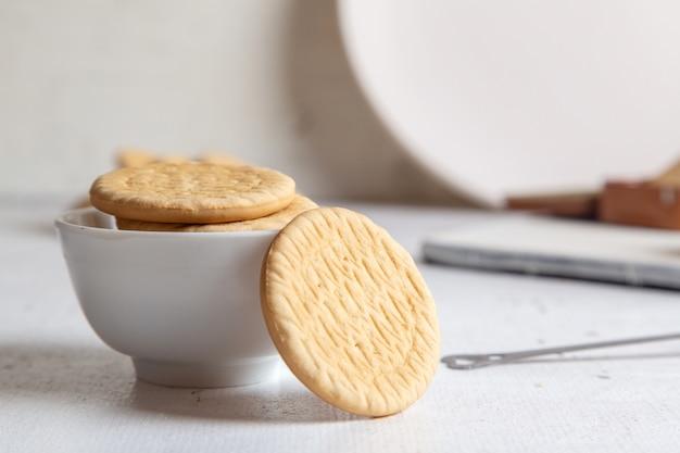 Vorderansicht von kleinen leckeren kuchen mit zuckerpulver und runden keksen auf der weißen oberfläche