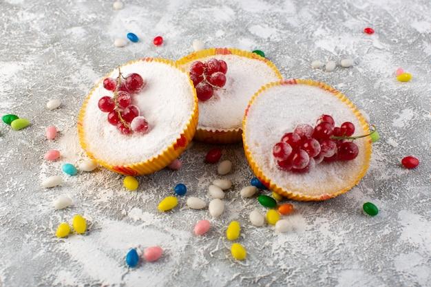 Vorderansicht von köstlichen cranberry-kuchen mit roten cranberries auf oberen zuckerstücken und pulver