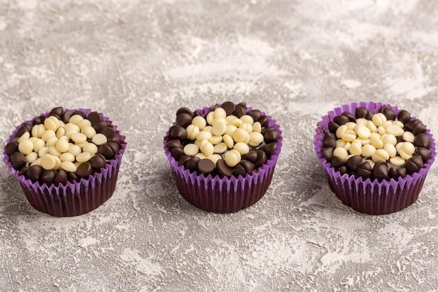 Vorderansicht von köstlichen schokoladenbrownies mit schokoladenstückchen auf der hellen oberfläche