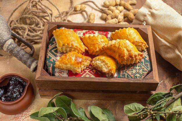 Vorderansicht von köstlichen süßen kuchen mit erdnüssen auf holzoberfläche