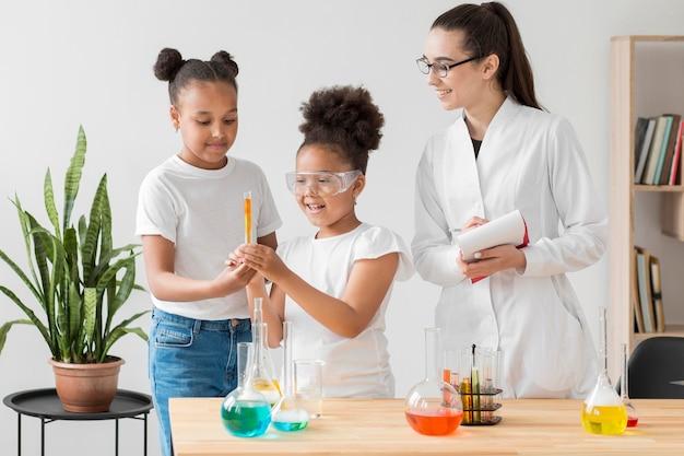 Vorderansicht von mädchen, die ein chemieexperiment mit wissenschaftlerin genießen