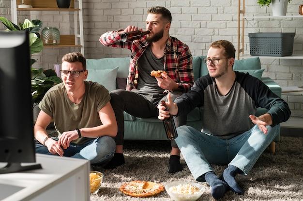 Vorderansicht von männlichen freunden, die pizza haben und sport im fernsehen mit bier beobachten