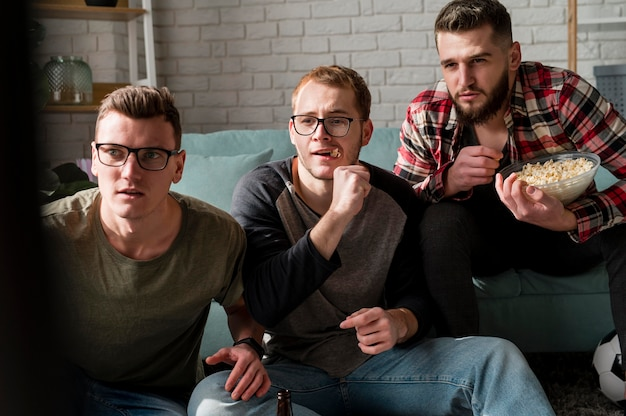 Vorderansicht von männlichen freunden, die sport im fernsehen beobachten und snacks haben