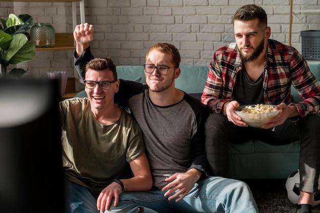 Vorderansicht von männlichen freunden, die sport im fernsehen beobachten und snacks zusammen haben