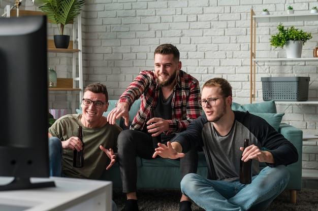 Vorderansicht von männlichen freunden, die sport im fernsehen zusammen ansehen