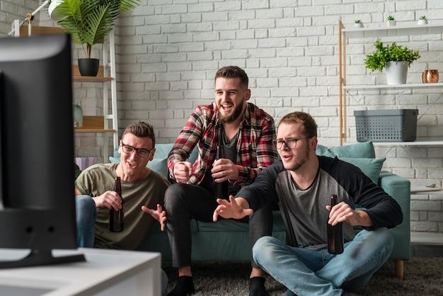 Vorderansicht von männlichen freunden, die sport zusammen im fernsehen ansehen