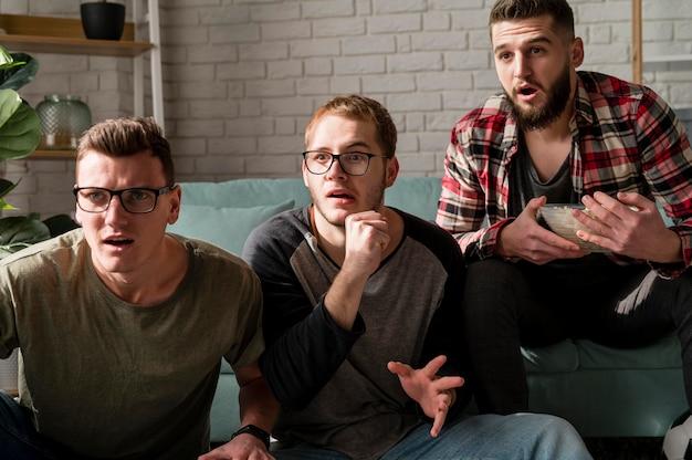 Vorderansicht von männlichen freunden, die zusammen sport im fernsehen schauen und snacks haben