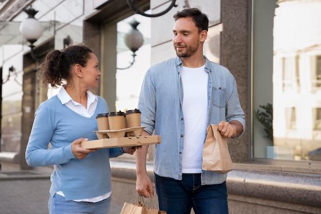 Vorderansicht von mann und frau im freien mit essen zum mitnehmen