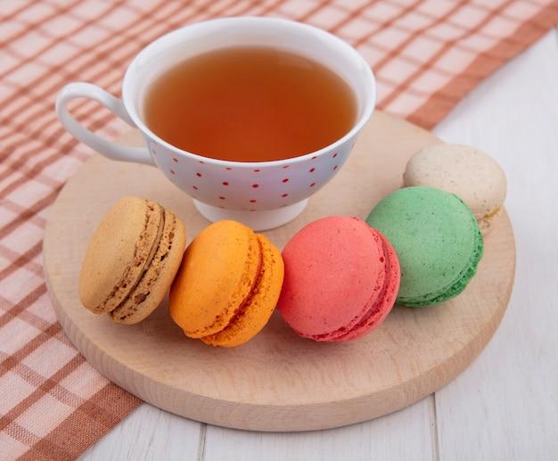 Vorderansicht von mehrfarbigen macarons mit einer tasse tee auf einem ständer auf einem braunen karierten handtuch