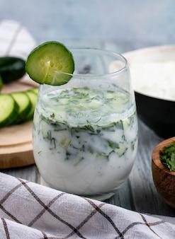 Vorderansicht von okroshka in einem glas mit einer gurke und einem weißen karierten handtuch