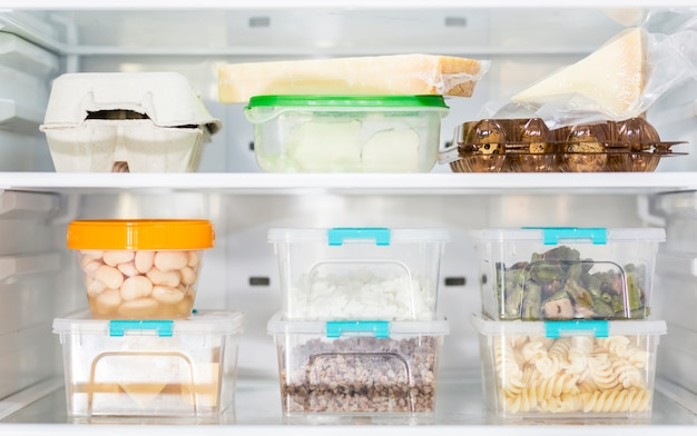 Vorderansicht von organisierten plastiknahrungsmittelbehältern im kühlschrank