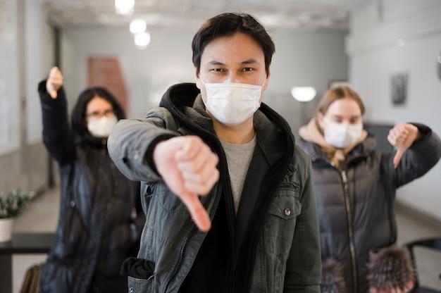 Vorderansicht von personen, die medizinische masken tragen und daumen nach unten geben