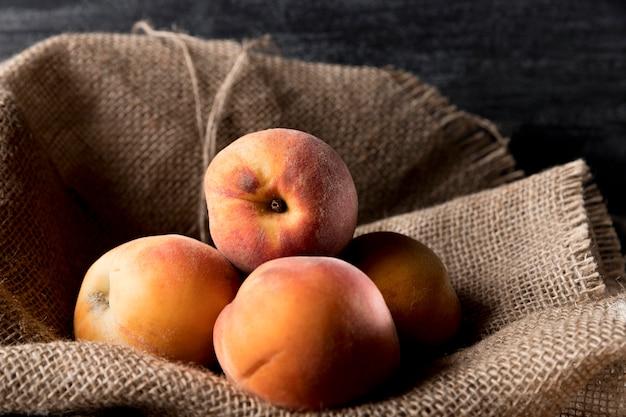 Vorderansicht von pfirsichen auf sackleinen