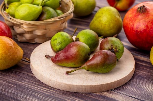 Vorderansicht von pfirsichen auf schneidebrett und im korb mit anderen und granatapfel auf holzoberfläche