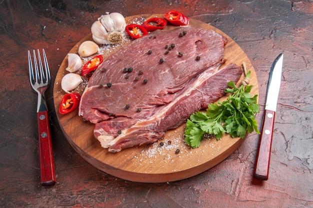 Vorderansicht von rotem fleisch auf holztablett und knoblauch, grüner zitronenpfeffer, zwiebelgabel und messer auf dunklem hintergrund