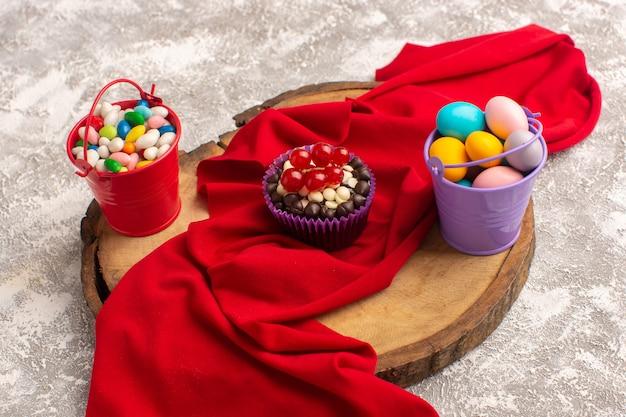 Vorderansicht von schokoladenbrownies mit verschiedenen bonbons auf der hellen oberfläche