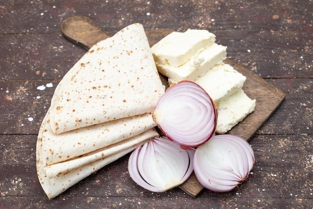 Vorderansicht von teig lavash mit zwiebeln und weißkäse auf der braunen holzoberfläche