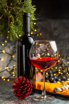 Vorderansicht von trockenem rotwein in einem glas und in einer flasche neben snack- und nadelbaumkegel auf grauem hintergrund