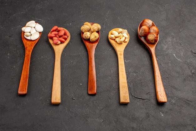 Vorderansicht von verschiedenen frischen nüssen erdnüssen und anderen nüssen auf löffeln auf dunkler oberfläche
