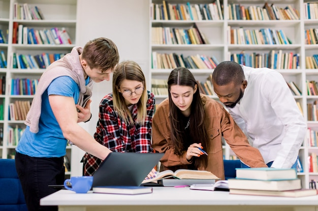 Vorderansicht von vier konzentrierten multiethnischen jungen leuten, studenten, die sich auf ihre hausaufgaben im bibliotheksraum vorbereiten