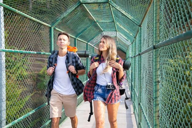 Vorderansicht von wanderern auf brücke mit grünem gitter umgeben. kaukasische touristen, die rucksäcke tragen und durch weg gehen. backpacking tourismus, abenteuer und sommerurlaub konzept