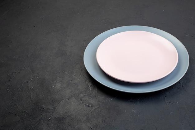 Vorderansicht von weißen und blauen keramischen leeren platten auf schwarzem hintergrund mit freiem platz