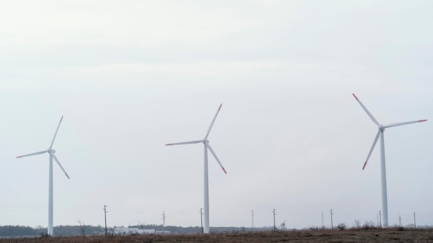 Vorderansicht von windkraftanlagen im feld, die elektrische energie erzeugen