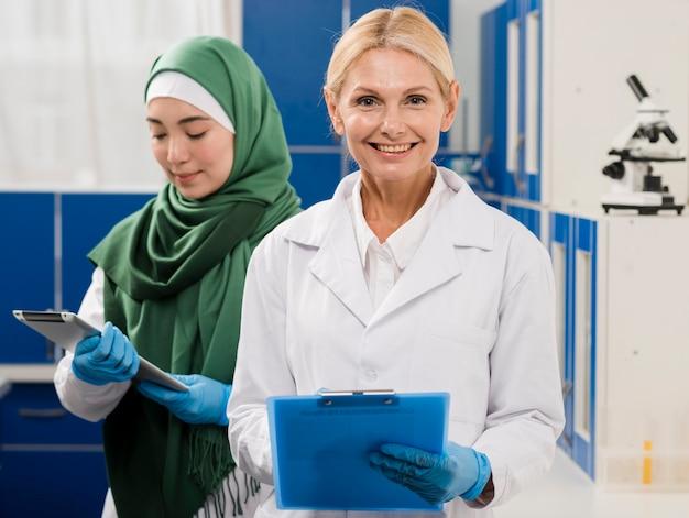 Vorderansicht von wissenschaftlerinnen, die im labor posieren