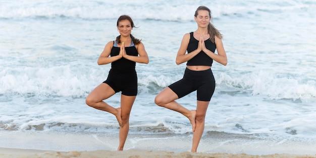 Vorderansicht von zwei frauen, die yoga neben ozean tun