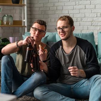 Vorderansicht von zwei männlichen freunden, die sport im fernsehen beobachten und bier haben