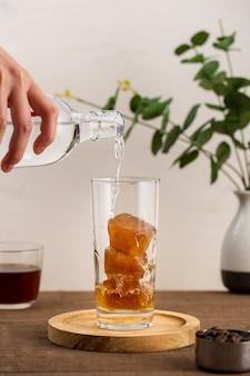 Vorderansicht wasser, das über eiskaffee fließt
