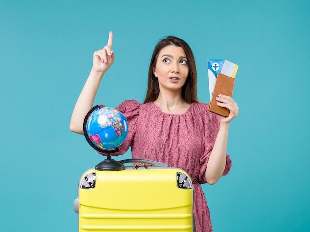 Vorderansicht weiblich im urlaub, der flugtickets auf dem blauen hintergrund seeurlaub frau reise reise reise hält