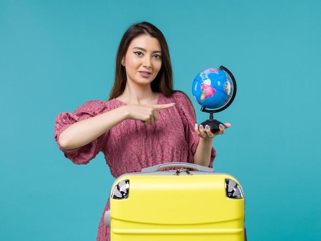Vorderansicht weiblich in der reise, die globus auf dem blauen hintergrundreise-reise-urlaubsreise-frauenmeer hält