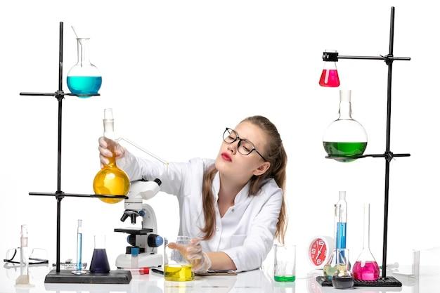 Vorderansicht weibliche chemikerin im medizinischen anzug, der flasche mit gelber lösung auf chemischem pandemie-covid-virus der weißen hintergrundchemie hält