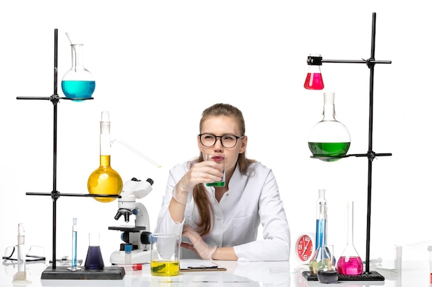 Vorderansicht weibliche chemikerin im medizinischen anzug, die geruch der lösung auf weißem hintergrundchemie-pandemie-gesundheitskovid prüft