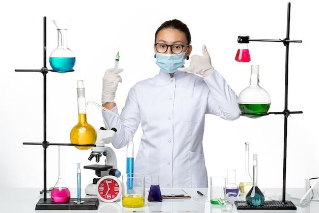 Vorderansicht weibliche chemikerin im medizinischen anzug mit maske, die injektion auf hellweißem hintergrundviruschemielabor-covid-spritzer hält
